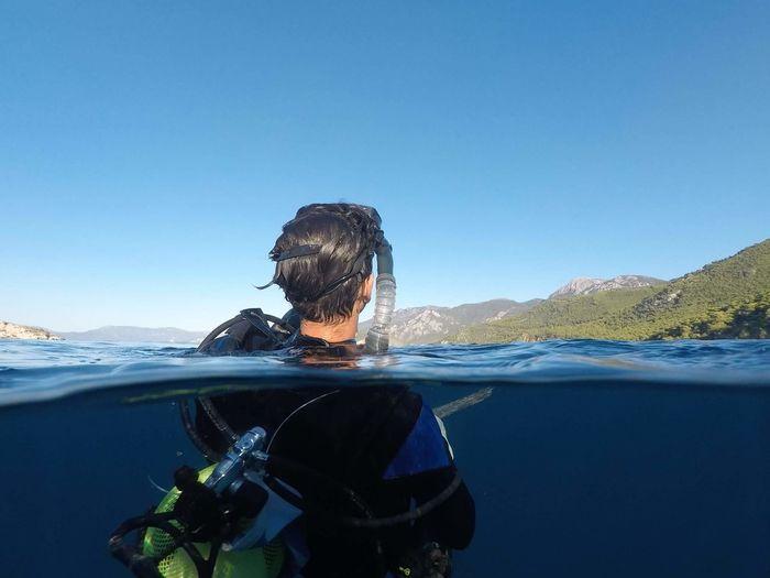 Scuba diver in sea against clear blue sky