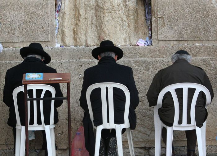 Rabbis Sitting On Chair In Of Front Wailing Wall