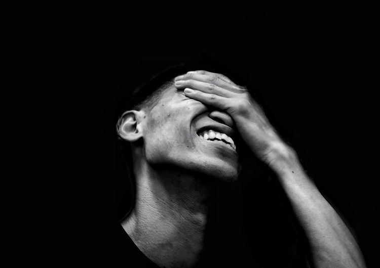 Woman with eyes closed against black background