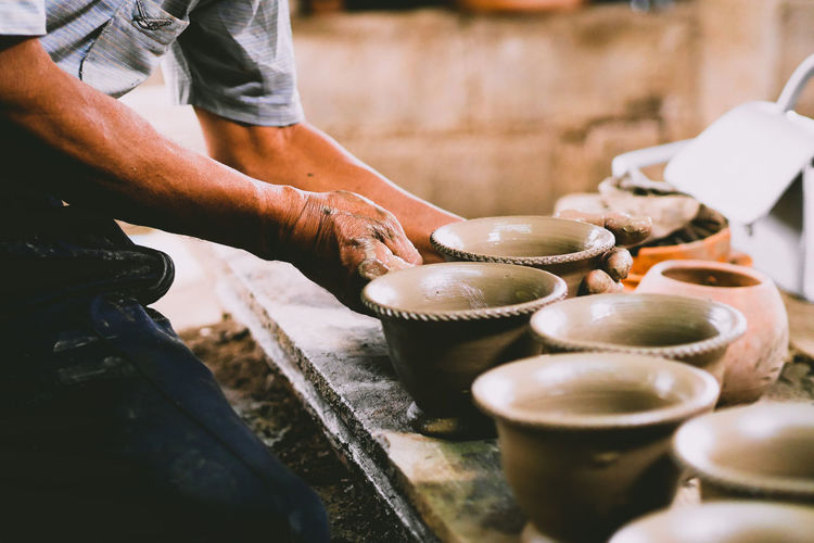 Midsection of man making pottery on table in workshop