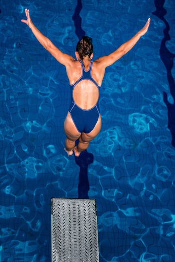 Female Diver Jumping Into The Pool Diving Diver Swimming Pool Woman Water Sport Training Competition Young Exercising Diving Board Board Above Action Swimwear Blue Activity Muscular Build Extreme Sports Caucasian Ethnicity Athlete Jumping Arms Raised One Person Lifestyles