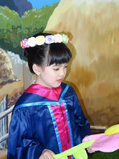 High angle view of girl in costume holding artificial flower