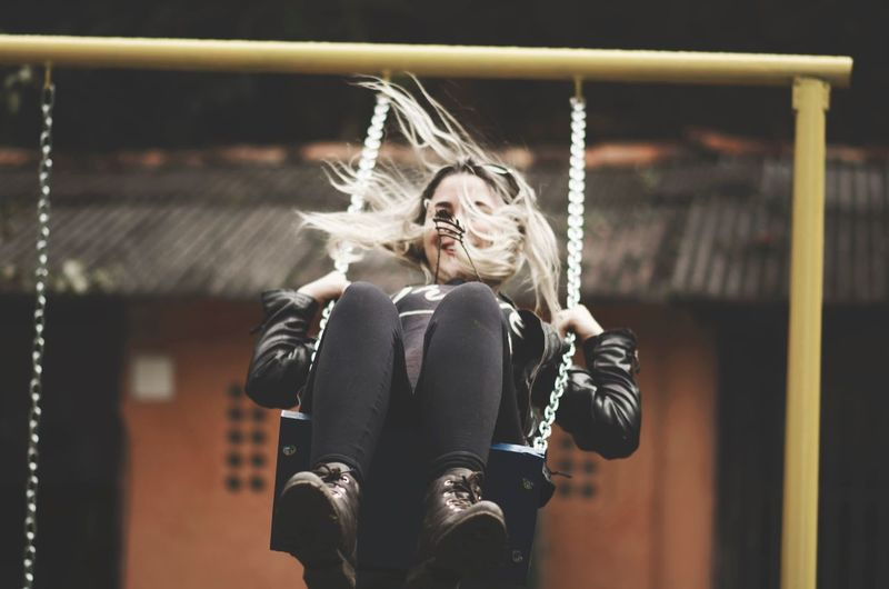 Young woman enjoying swing against building
