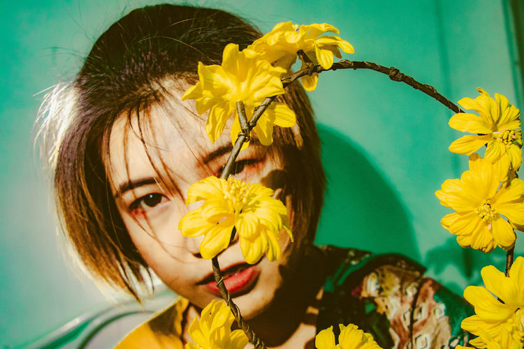 Portrait of woman by yellow flowers sitting at home
