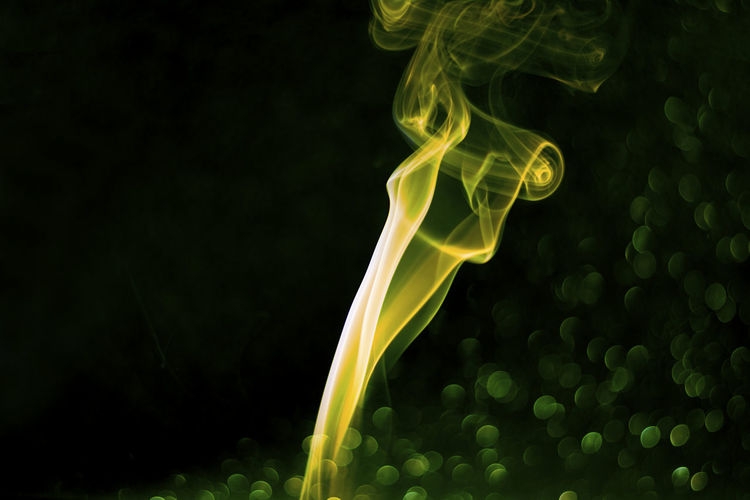 Close-up of green smoke against black background