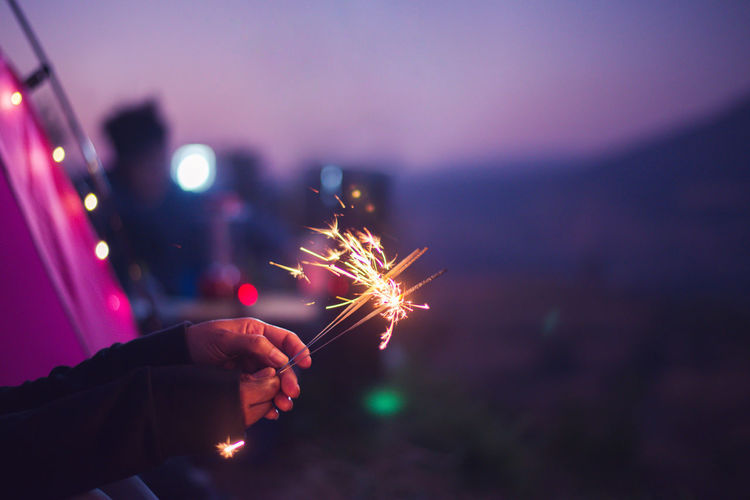 Cropped hand of person holding illuminated sparklers