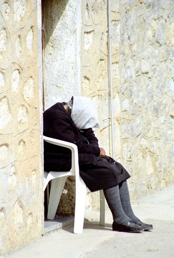 Woman with covered face resting on chair by wall