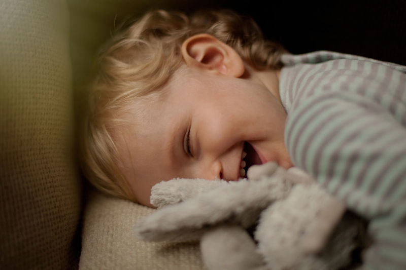 Close-up of cute baby boy laughing on sofa at home