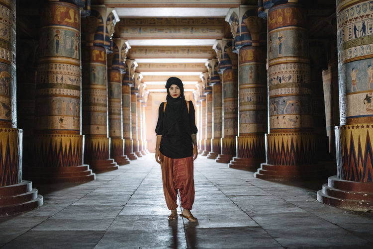 Full length portrait of woman wearing scarf standing by architectural columns