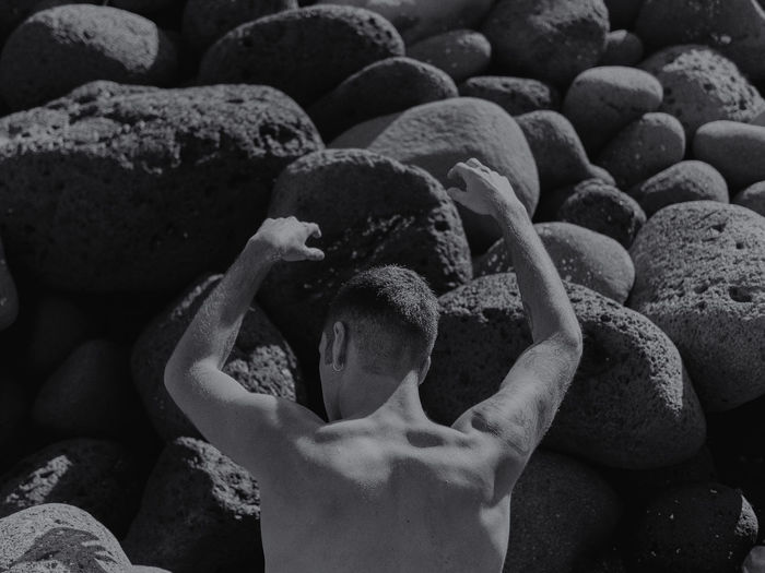 Rear View Of Shirtless Man Standing Against Rocks