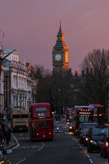 Vehicles on street against big ben at sunset