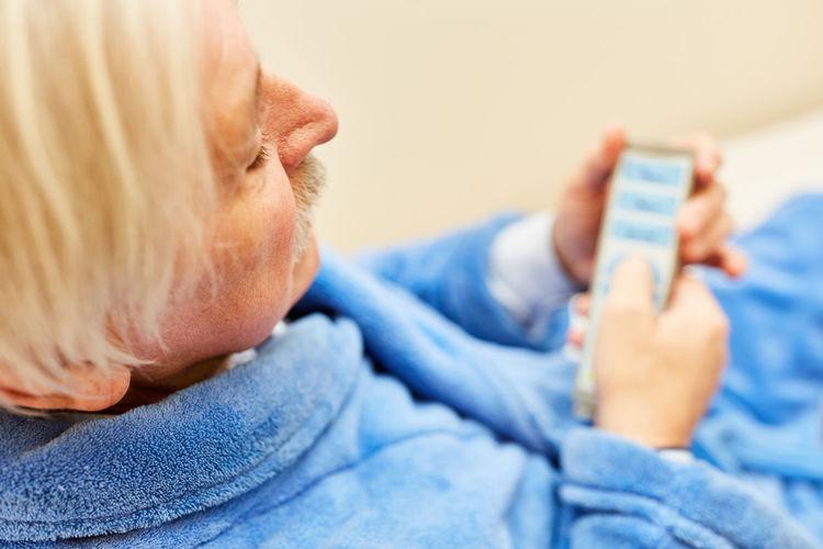 Senior man wearing bathrobe holding remote control while sitting at nursing home