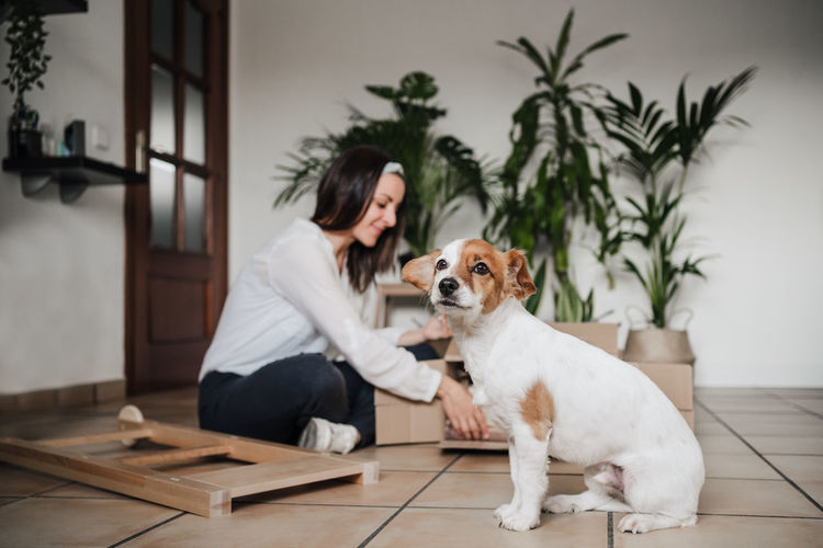 Woman with dog sitting on table at home