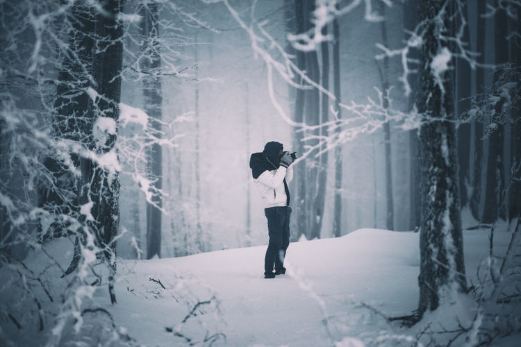 Woman standing on snow covered forest