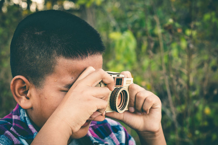 Close-up of boy photographing through camera against plants