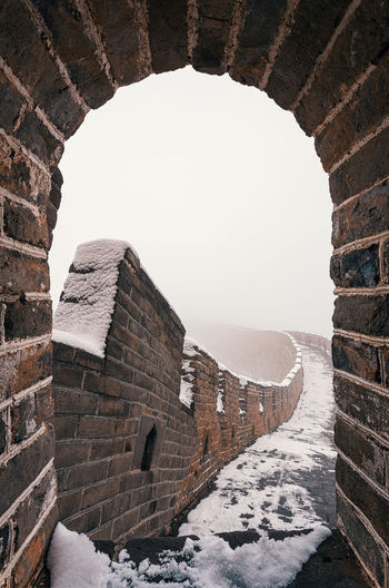 Arch leading towards walkway with snow against clear sky during winter