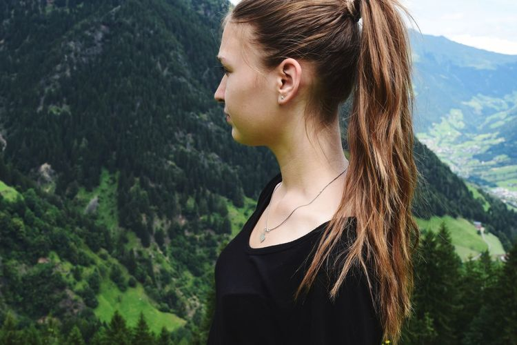 Side view of beautiful woman standing against mountain