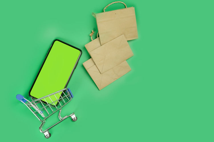 High angle view of mobile phone against green background
