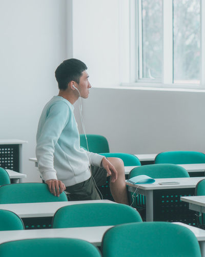 Side view of young man listening music while sitting on table in classroom