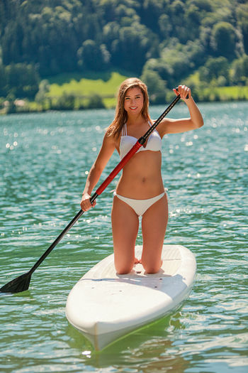 Beautiful young woman in bikini, kneeling on a board, paddling on a lake SUP Board Stand Up Paddling Beauty In Nature Bikini Blond Hair Board Day Lake Leisure Activity Lifestyles Nature Oar One Person Outdoors Paddel People Real People Smiling Summer Swimwear Vacations Water Women Young Adult Young Women