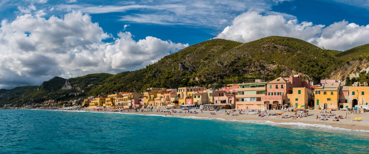 Panoramic view of Varigotti, small sea village near Savona, with crowded beach during a sunny afternoon Cityscape Coastline Houses Mediterranean  Promenade Savona  Skyline Varigotti View Beach Building Exterior Clouds Coast Day Italy Landscape Liguria Riviera Sand Scenics Sea Sky Summer Village Waterfront