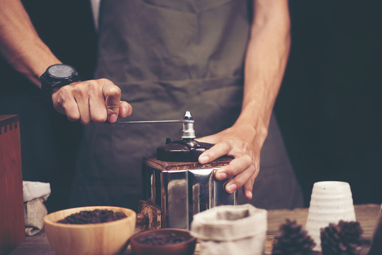 Midsection of barista grinding coffee