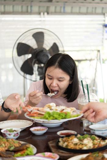 Woman eating food in restaurant