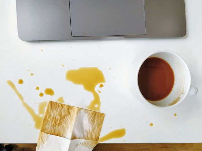 High angle view of spilled coffee and cup on desk and laptop