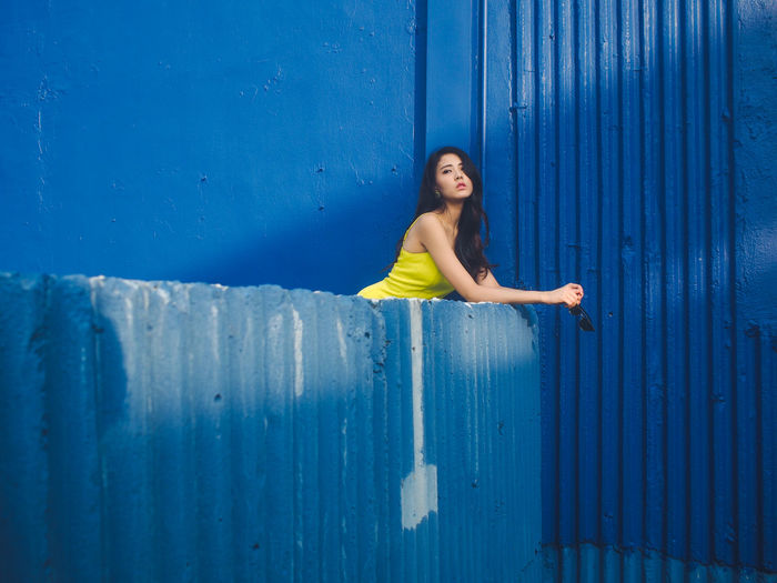 Portrait of smiling girl standing against blue wall