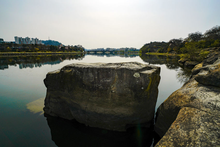 """Uiam, which literally means """"Righteous Rock,"""" is a large rock where Nongae, a gisaeng (a young woman trained in the arts of music, dancing, and poetry to act as a professional companion for aristocratic men), killed a Japanese military leader by jumping off a cliff into Namgang River while grasping him tightly. She took action just after the Second Jinjuseong Battle in 1593 as an attempt to avenge about 70,000 soldiers, government officials, and civilians who were killed by the Japanese forces that invaded Korea (then Joseon) in 1592. The name of the rock, inspired by Nongae's loyal, patriotic act, was given by the local people who admired her heroism. On the western face of the rock is its name written in seal script in 1629 by local Confucian scholar and calligrapher Jeong Dae-ryung (1599-1661); on the southern face is the second inscription, written in regular script by another calligrapher named Han Mong-sam (1598-1662). The upper surface of the rock measures 3.5 by 3.3 square meters. Historical Site Japanese Invasion Of Korea In 1592 ND Filter Namgang Nongae Righteous Rock Riverside Rock Historical Place Jinju Object Solid Uiam Water 一帶長江 千秋義烈 壬辰倭亂 毛谷村六助 義巖 論介 남강 논개 의암 임진왜란 진주 진주성"""