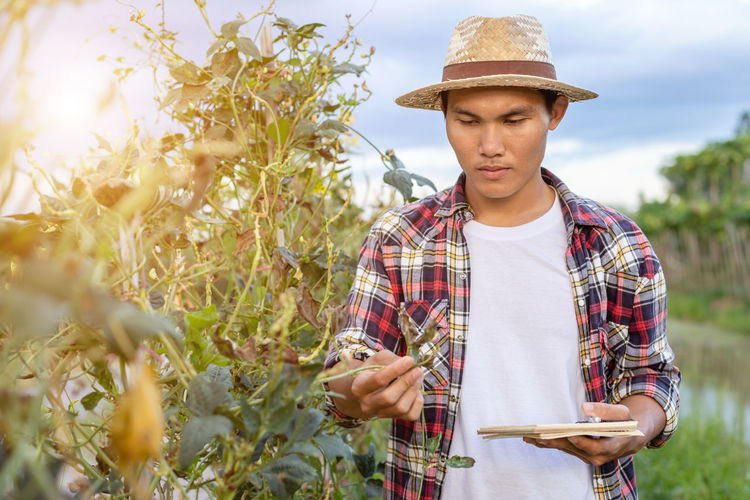 Young man wearing hat while standing by plants
