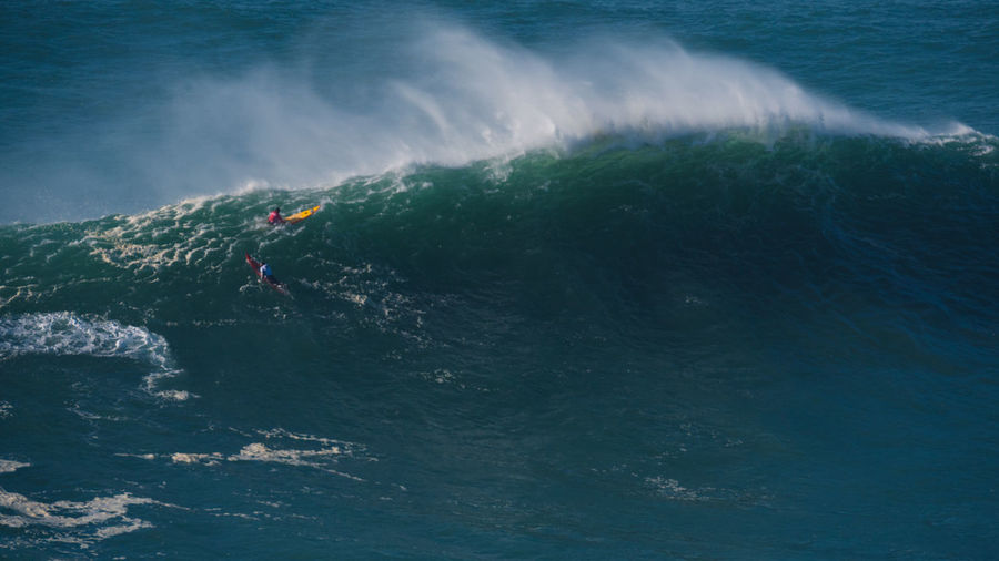 High Angle View Of Surfers Surfing On Wave In Sea