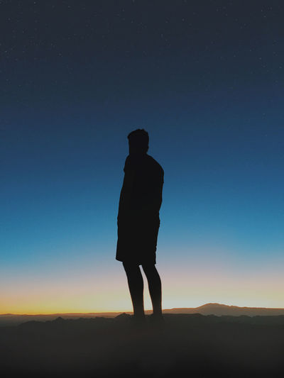 Silhouette of man standing on landscape at sunset