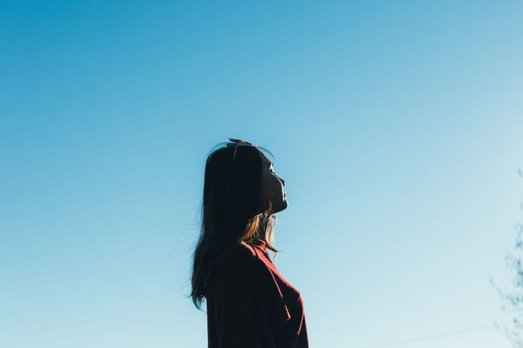 Side view of young woman standing against clear blue sky