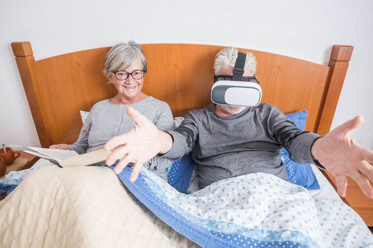 High Angle View Of Senior Couple On Bed At Home