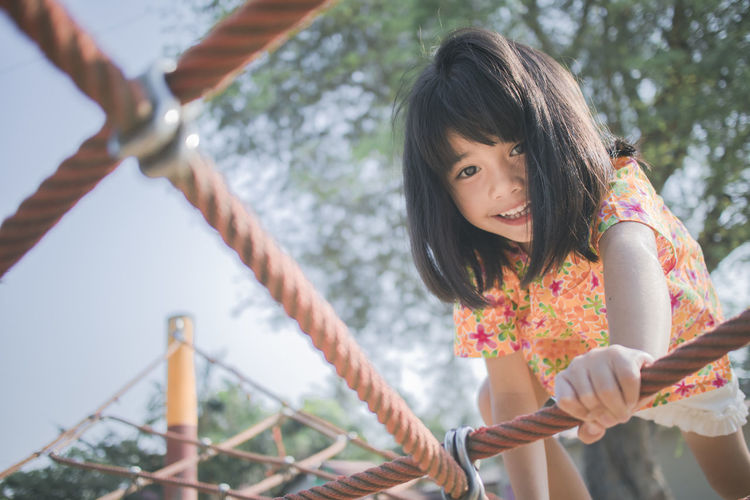 Low angle portrait of smiling girl climbing jungle gym in playground
