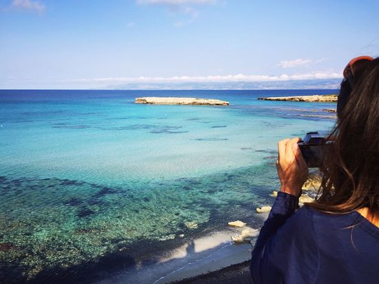 Blue Lagoon at Akamas peninsula in Cyprus Sea Horizon Over Water Real People Water Sky One Person Photographing Beauty In Nature Rear View Nature Beach Day Outdoors Women Standing Leisure Activity Peyia Paphos Cyprus Rocks Girl Weather Mideterranian Lagoon Nature