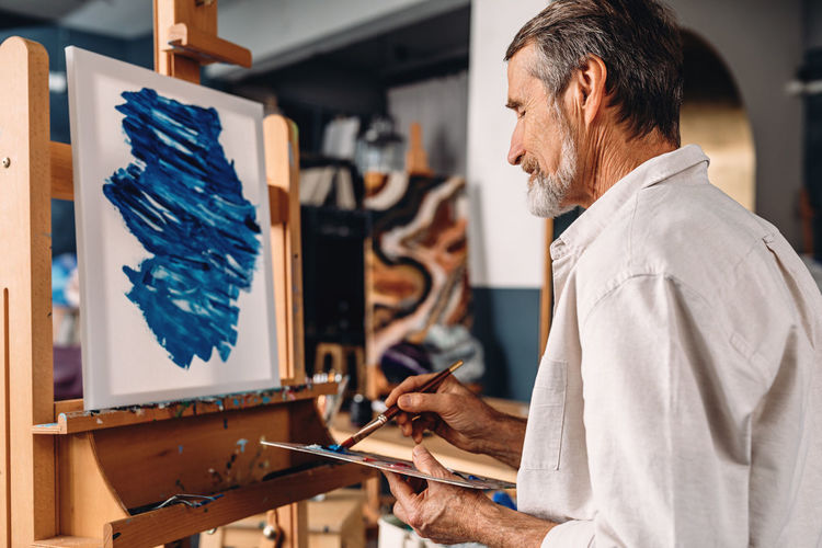 Senior man with paintbrush painting at workshop