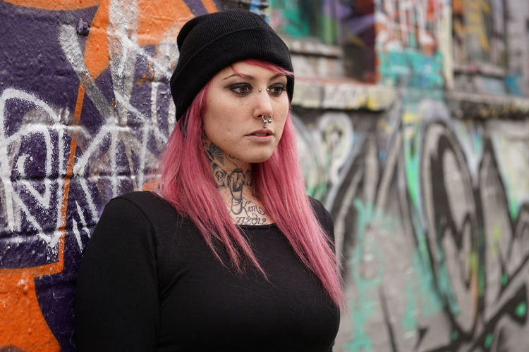 Young woman with pink hair standing against graffiti wall