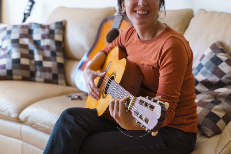 Woman playing guitar on sofa at home