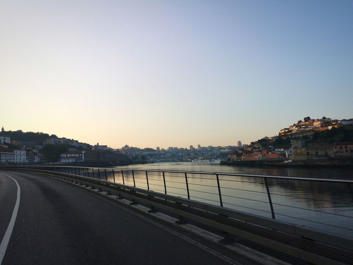 Road by river and buildings against clear sky