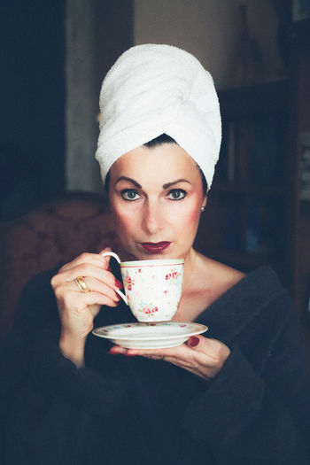 Portrait of woman drinking coffee while wearing robe