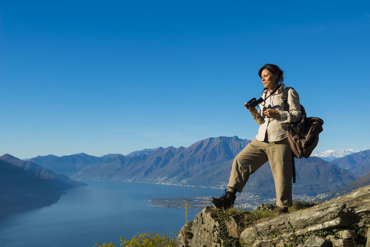 Woman Standing on Mountain Top and Taking Photos Over Alpine Lake Maggiore and Mountain in Ticino, Switzerland. Adult Camera - Photographic Equipment Clear Sky Exploring High Up Hiking Panoramic View Standing Sunny Woman Adventure Alpine Lake Backpack Day Elevated View Lake Maggiore Mountain Mountain Range Mountain Top One Person One Woman Only Outdoors Swiss Alps Using Camera Valley