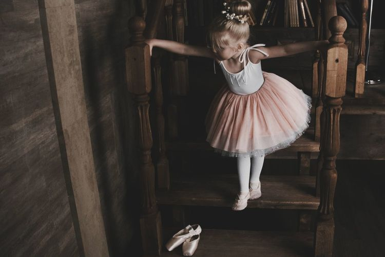 High angle view of ballet dancer standing on steps at home