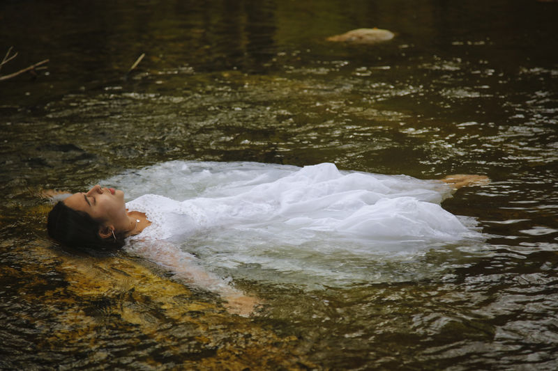 Side view of man lying in water