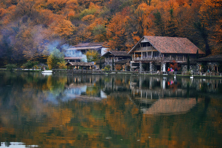Houses by lake against trees during autumn