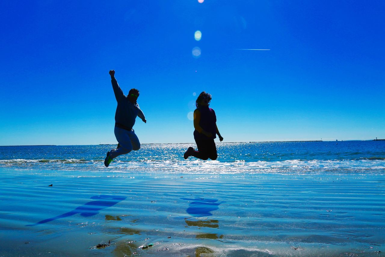 real people, water, two people, leisure activity, lifestyles, sea, blue, fun, beauty in nature, nature, togetherness, enjoyment, vacations, scenics, horizon over water, sky, full length, men, outdoors, day, beach, clear sky, women, young women, friendship, young adult, people