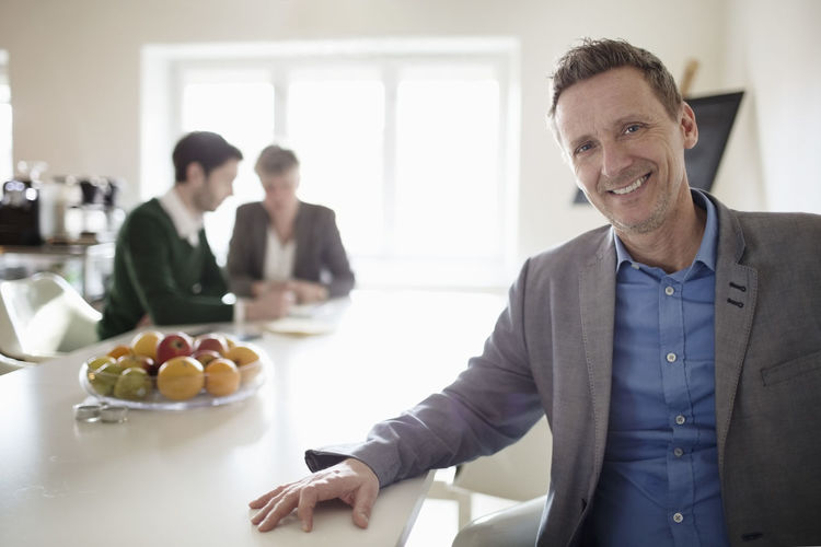 Portrait of a smiling man with food on table
