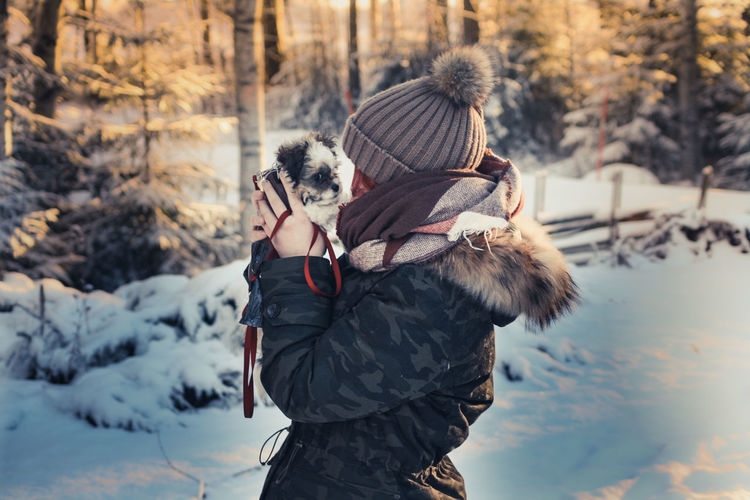 Side view of woman carrying puppy while standing on snow in forest during winter