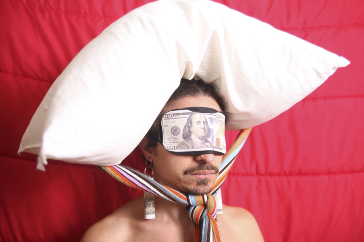 Man with pillow tied on head while wearing paper currency sleep mask